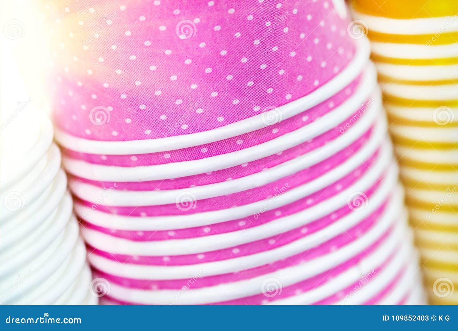 Пестротканые бумажные стаканчики Яркие еда и предпосылка питья Стог красочных контейнеров Закройте вверх по куче стекел
