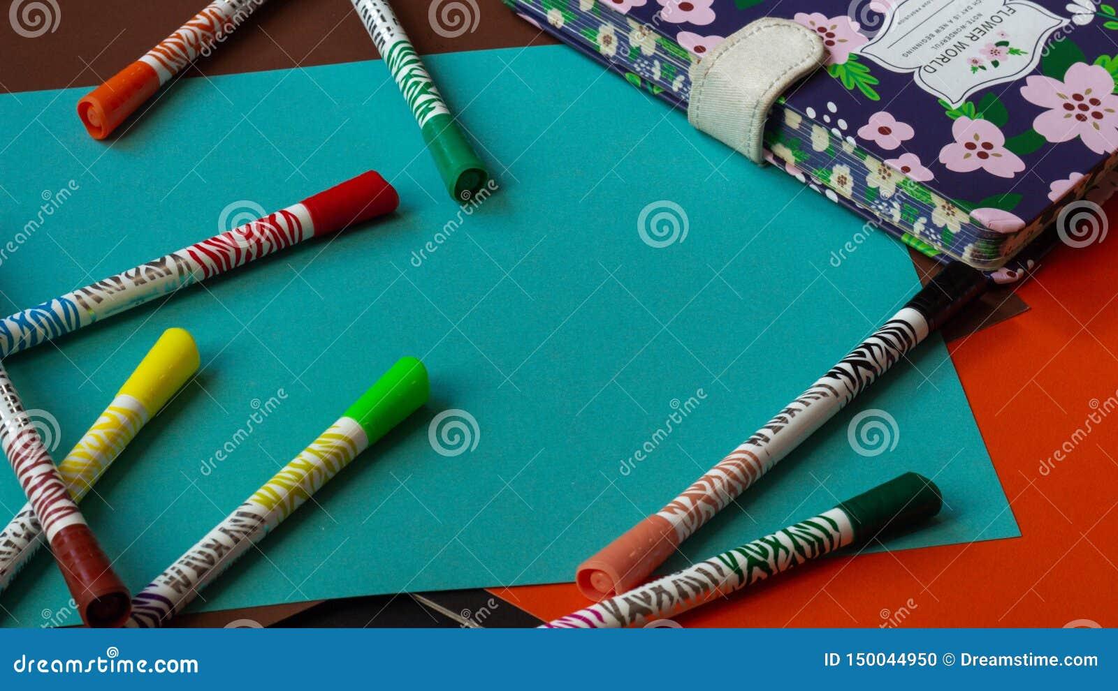 Пестротканые ручки войлок-подсказки лежат на красочном ярком картоне рядом с блокнотом