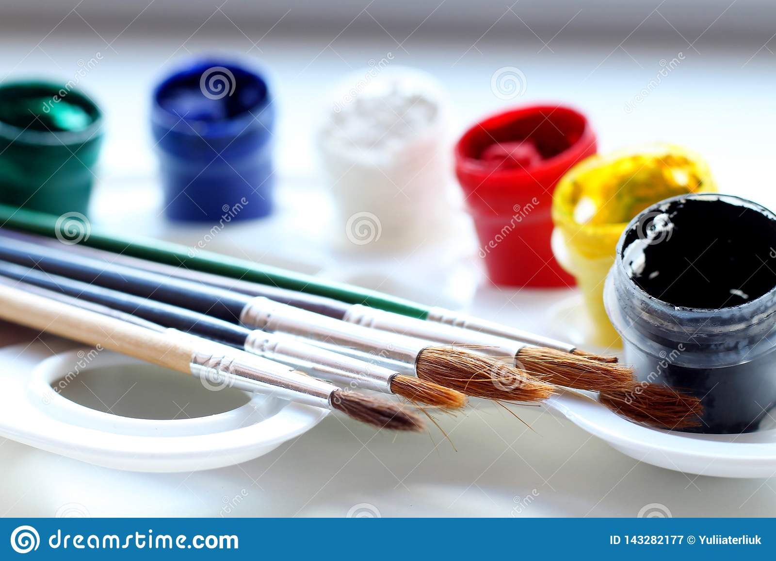 Пестрые краски с щетками на белой палитре