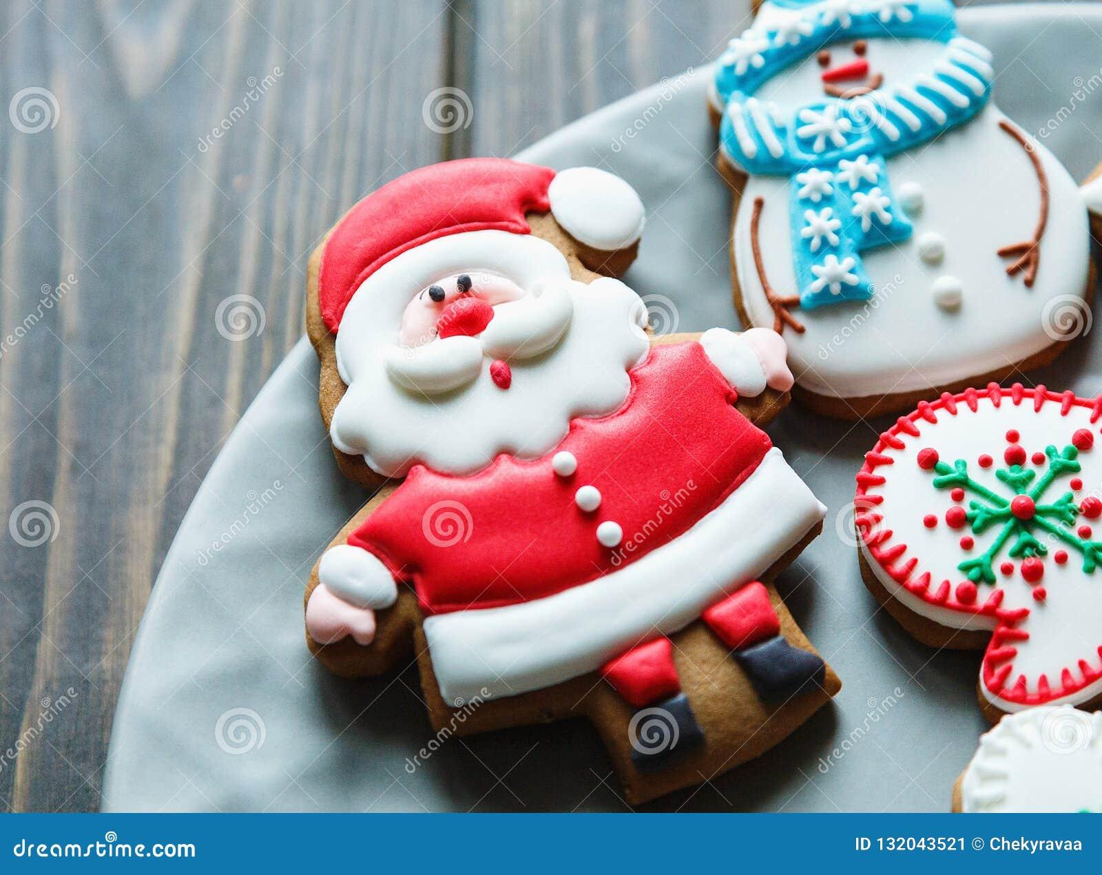 Печенья пряника рождества домодельные, специи на плите на темной деревянной предпосылке среди подарков на рождество, взгляде свер