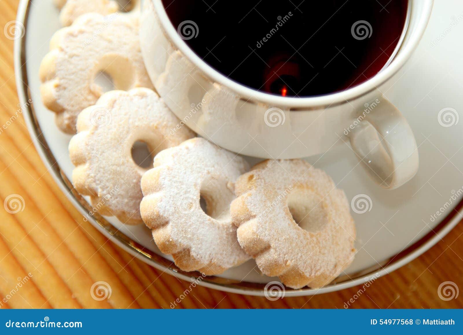Печенья Canestrelli итальянки на поддоннике чашки черного чая