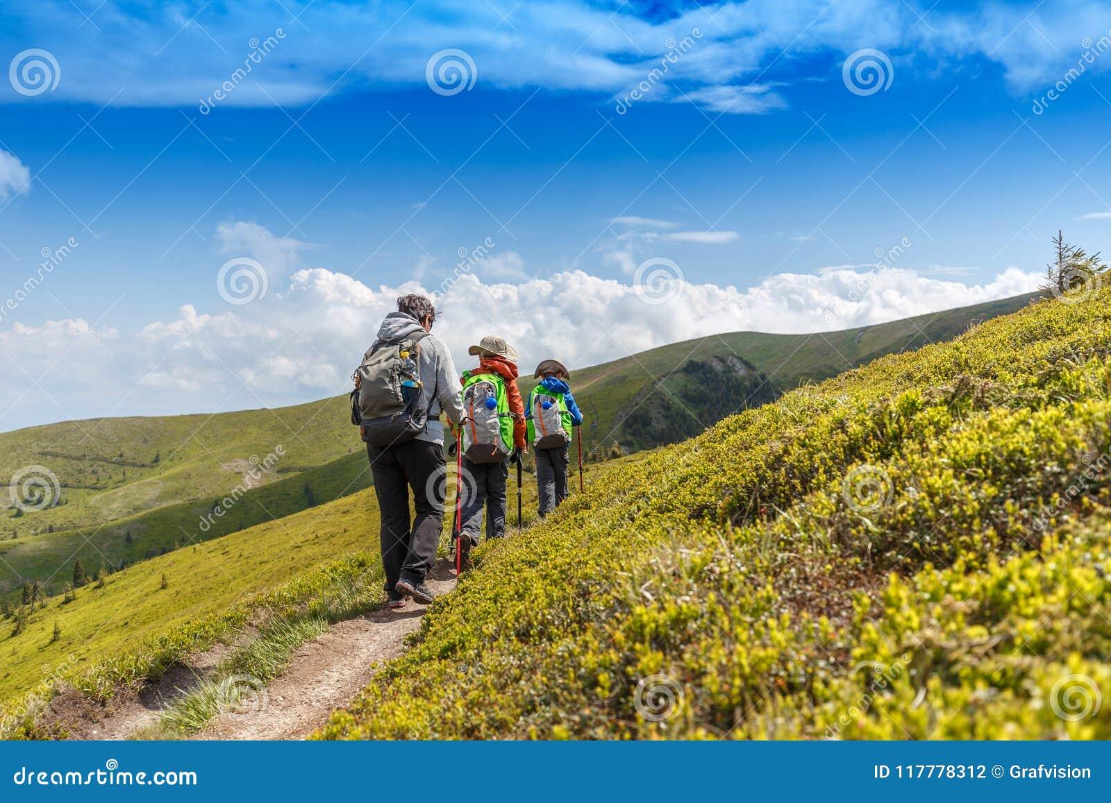Пешая женщина с ее детьми в румынских горах
