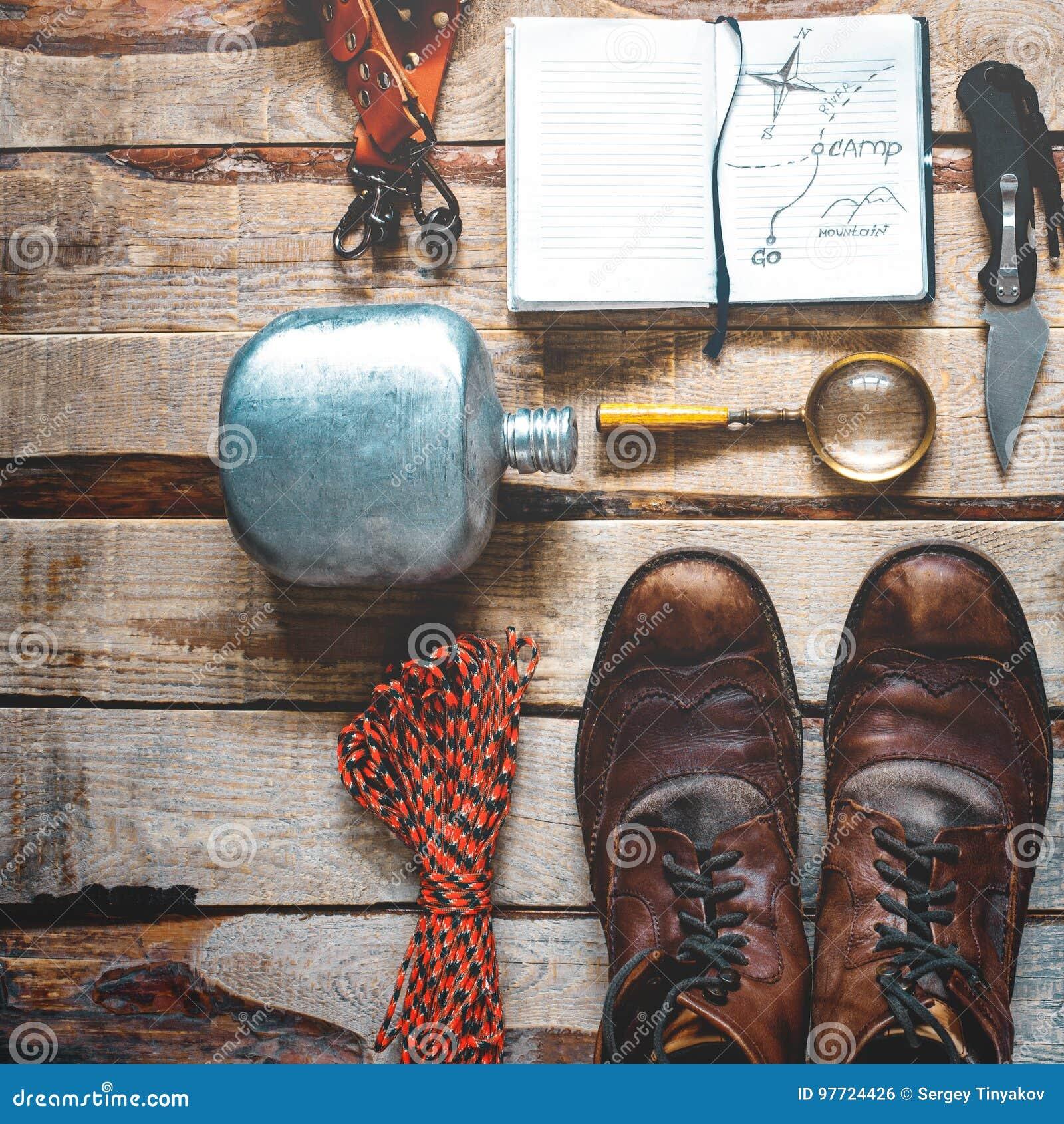 Пешие аксессуары на деревянной предпосылке: старые пешие кожаные ботинки, винтажная камера фильма, тетрадь перемещения, нож Конце