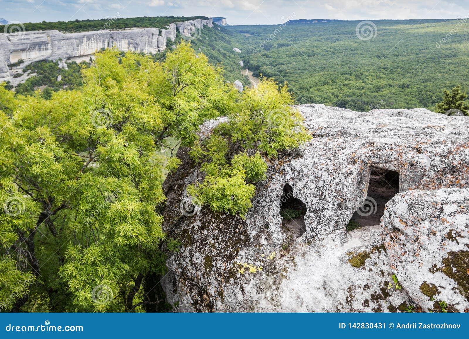 Пещера на верхней части горы, взгляде леса и долине