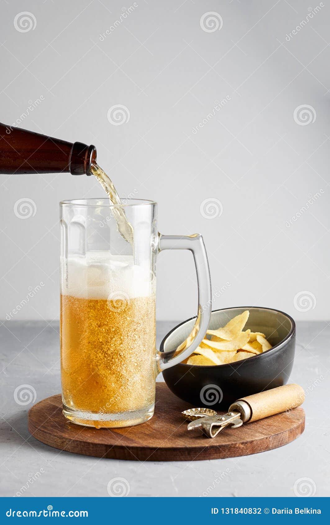 Пиво лагера лить в стекле и бутылке с картофельными чипсами