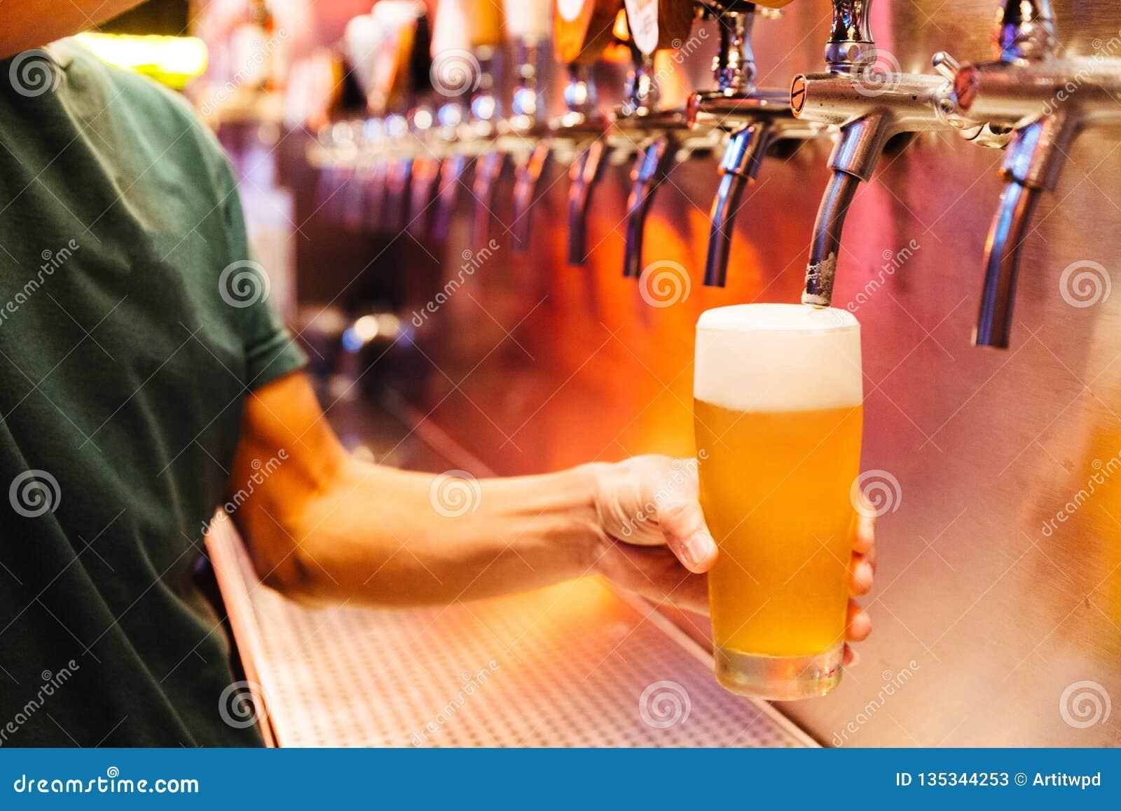 Пиво ремесла человека лить от кранов пива в замороженном стекле с пеной Селективный фокус Концепция спирта сбор винограда типа ли