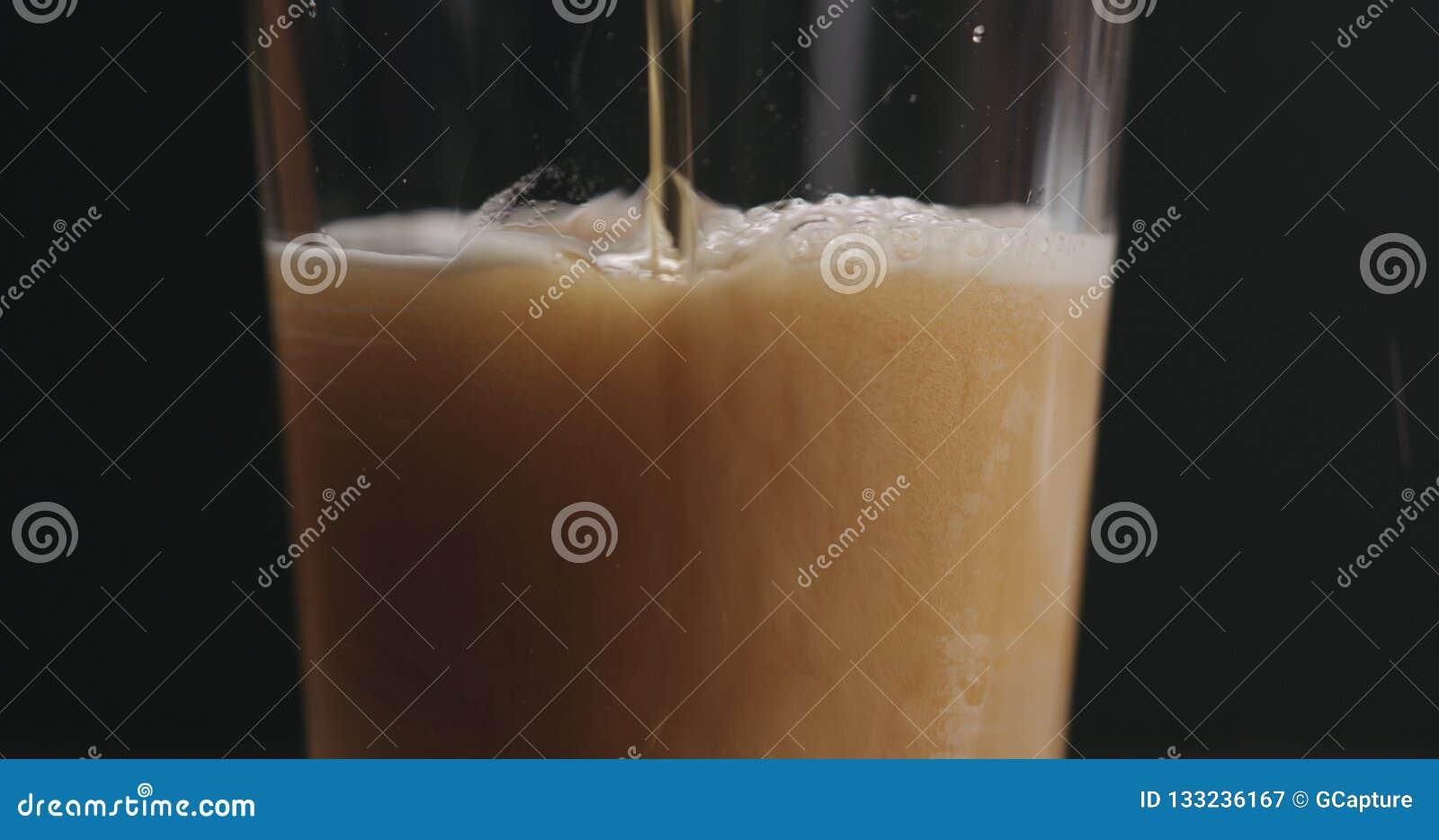 Пиво эля крупного плана лить в стекле над черной предпосылкой