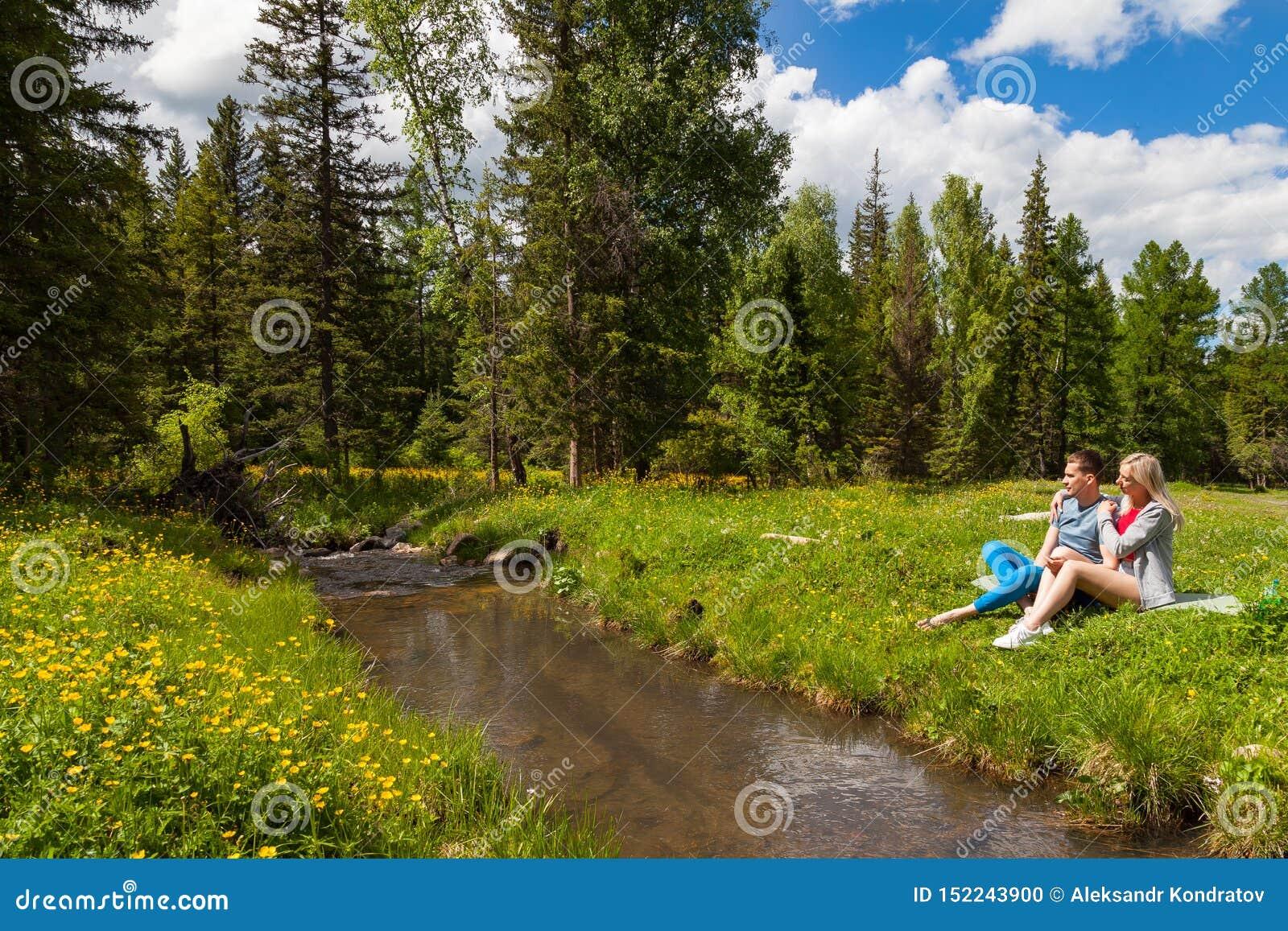 Пикник на банке реки горы с зеленой травой и желтыми цветками на фоне хвойных деревьев и сини