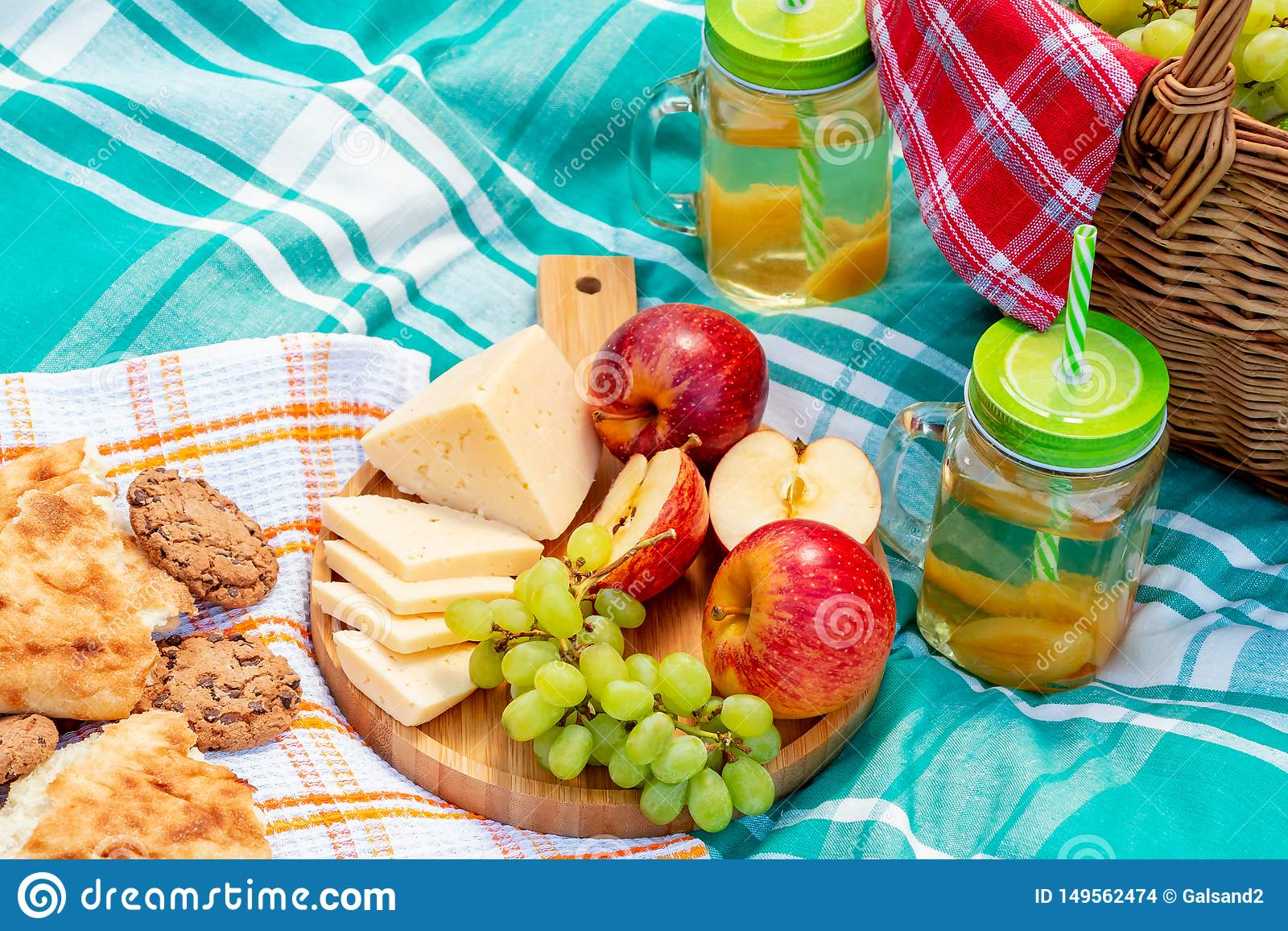 Пикник на траве на летний день - корзине, виноградинах, сыре, хлебе, яблоках - концепция воссоздания лета на открытом воздухе