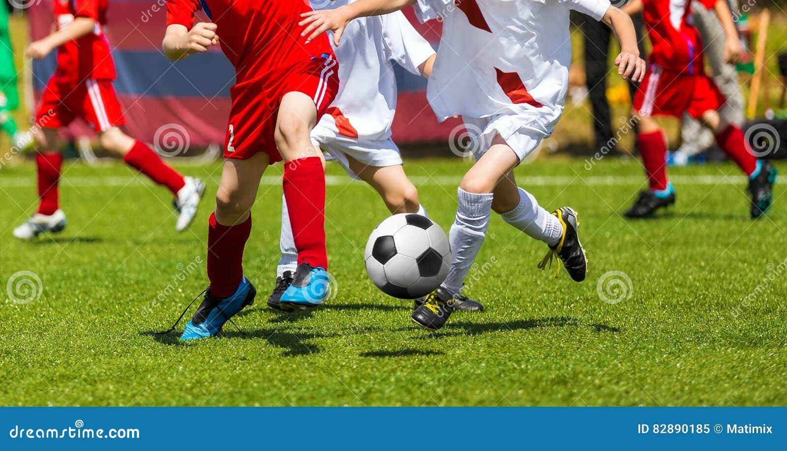 Пинок футбола футбола Поединок футболистов Дети играя футбольную игру на спортивной площадке Футбольный матч игры мальчиков на зе