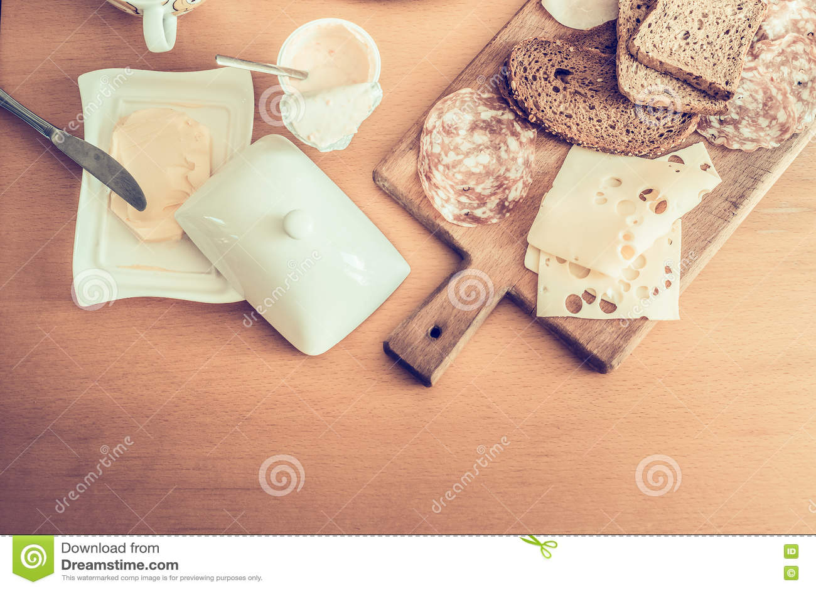 Питательный завтрак, ингридиенты для делать сандвичи с салями, масло и сыр, югурт на взгляд сверху деревянного стола