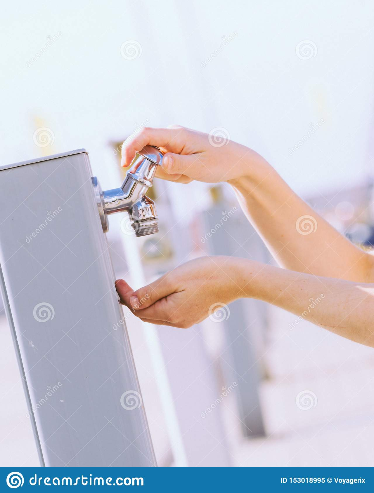 Питьевая вода женщины от крана улицы