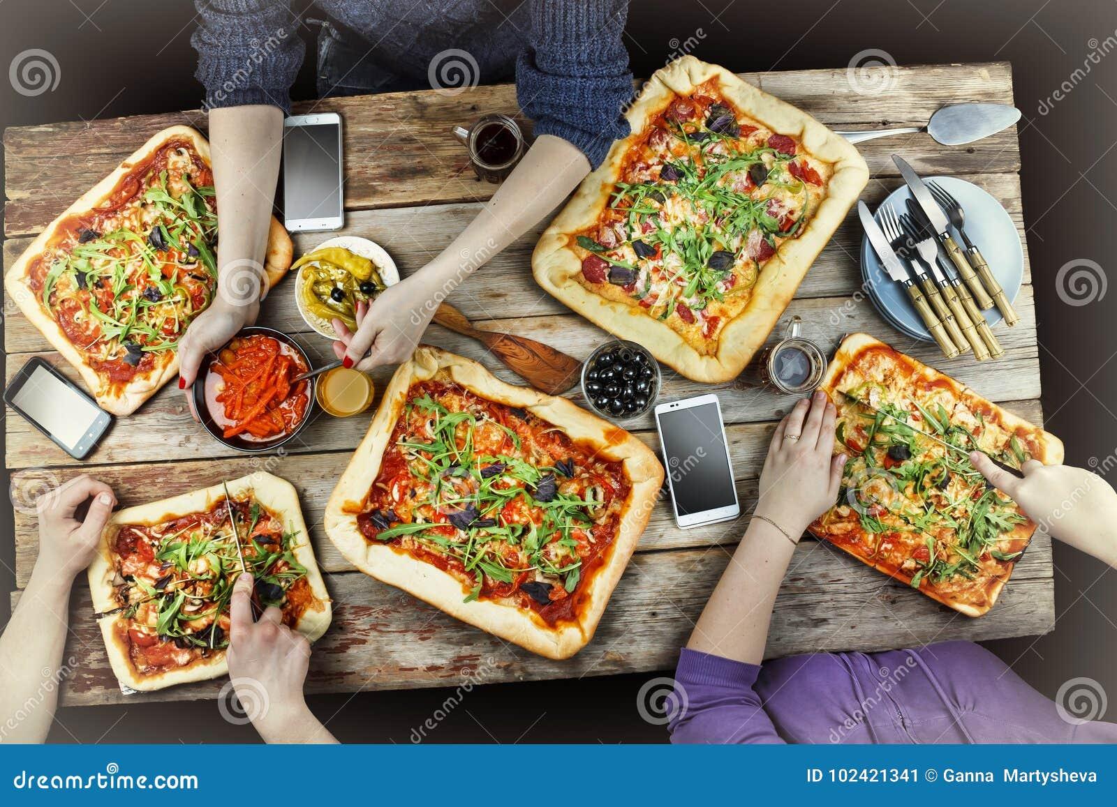 Пицца вырезывания Отечественная еда и домодельная пицца Наслаждаться обедающим с друзьями Взгляд сверху группы людей имея обедающ
