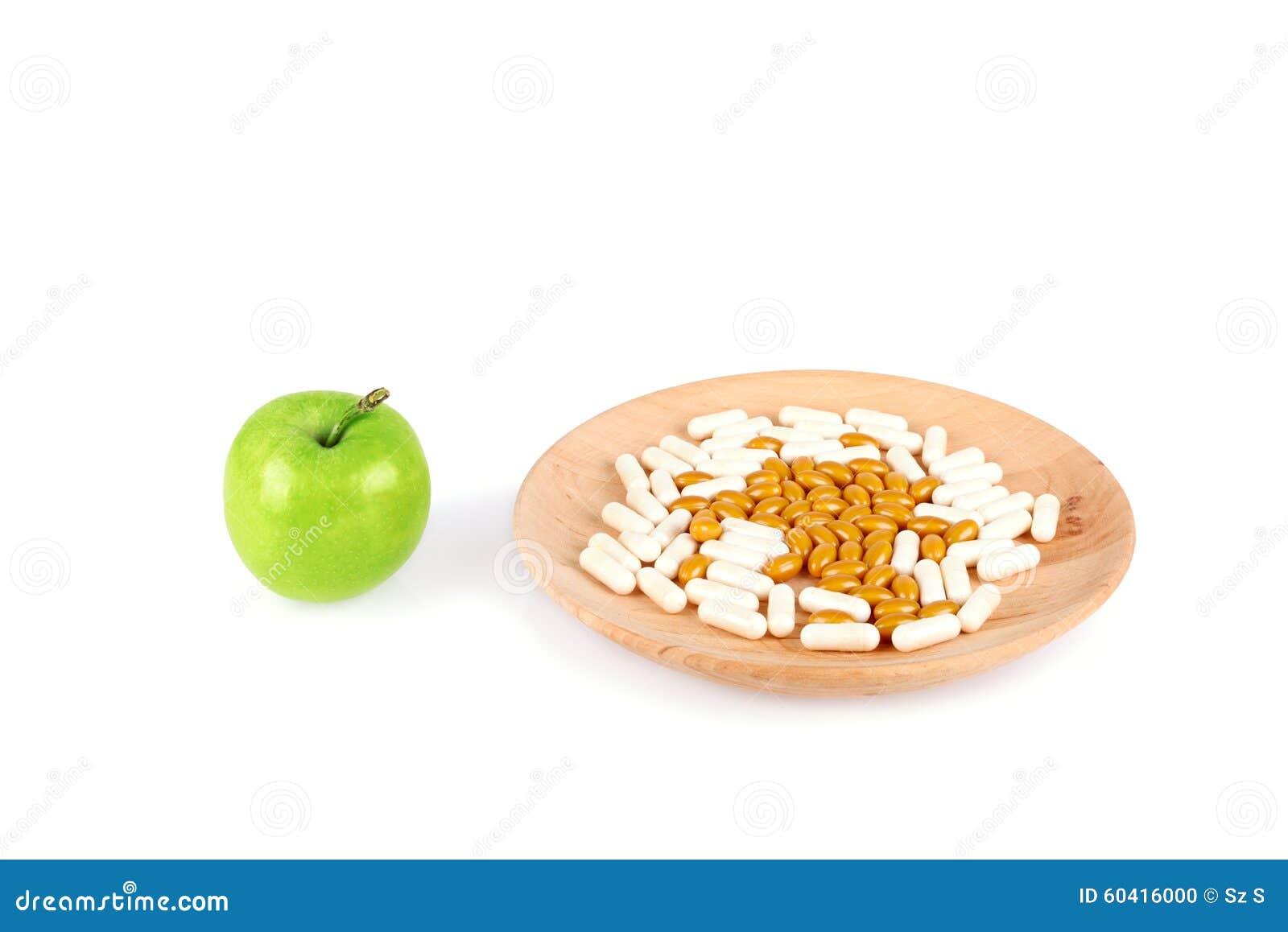 Пилюльки на деревянной плите и яблоке изолированном на белизне
