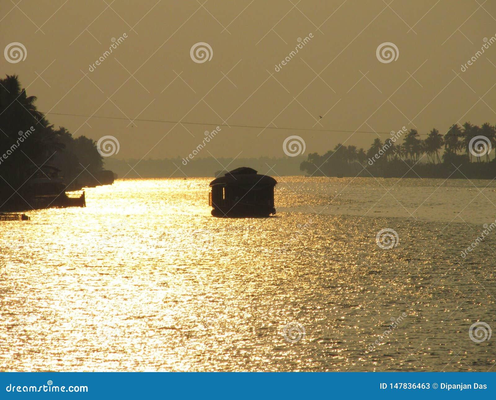 Плавание плавучего дома во время захода солнца на подпорах Alleppy, Кералы, Индии