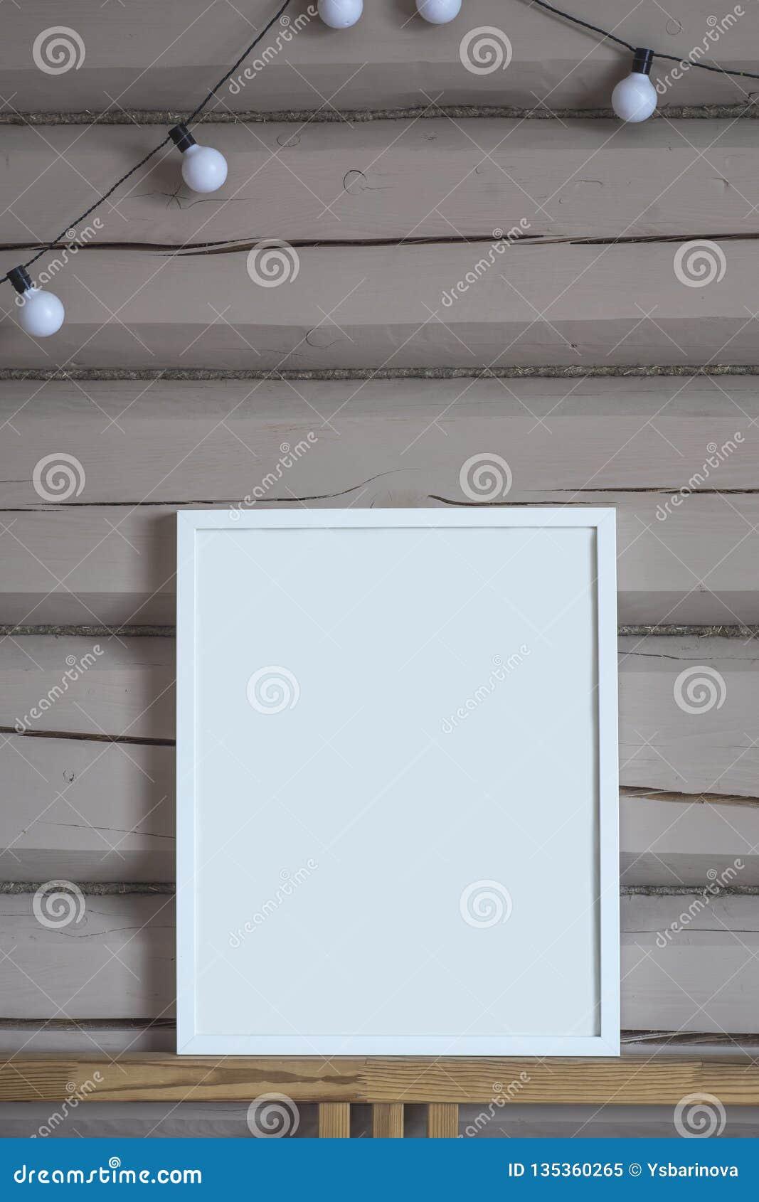 Плакат белой бумаги пустой внутренний, изолированная вертикальная насмешка вверх с рамкой на бежевой деревянной предпосылке стены