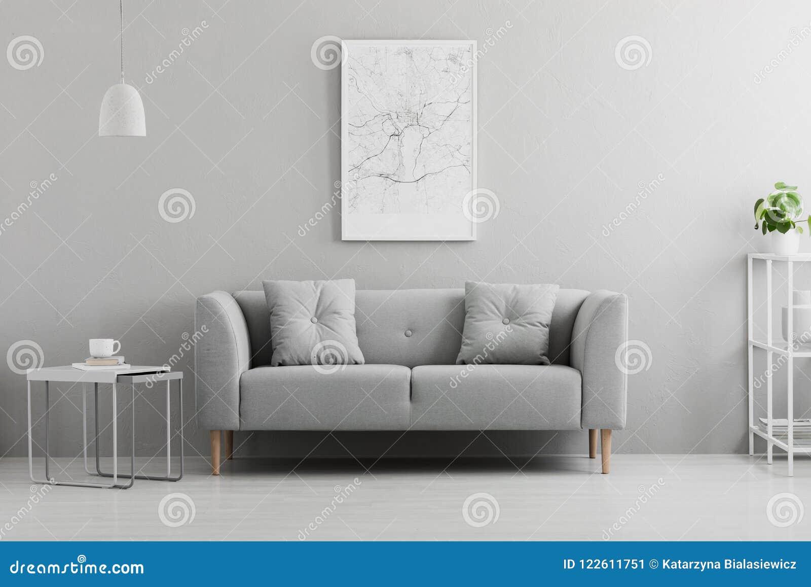 Плакат над серым креслом в минимальном интерьере живущей комнаты с таблицей лампы вышеуказанной Реальное фото