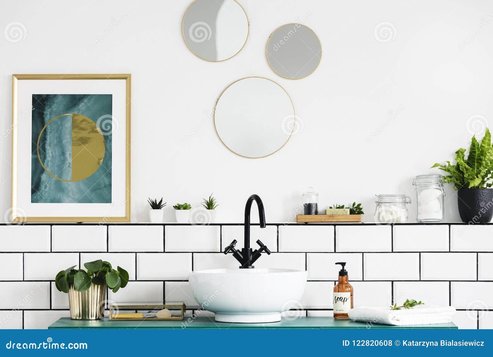 Плакат рядом с круглыми зеркалами над washbasin и заводом в белом интерьере ванной комнаты Реальное фото
