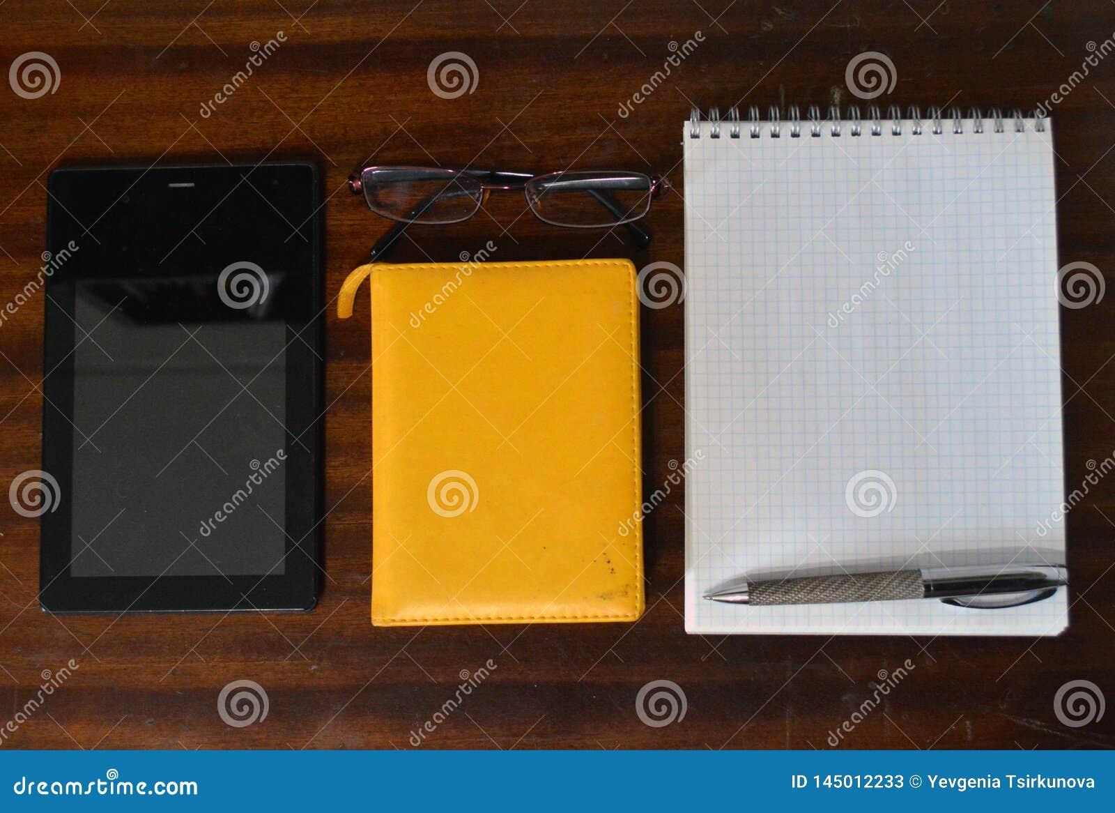 Планшет, блокноты, стекла и ручка металла на темном деревянном столе