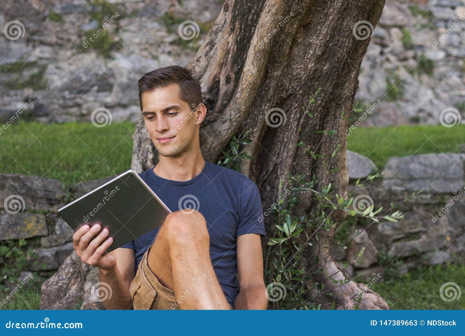 Планшет чтения человека и насладиться остатками в парке под деревом