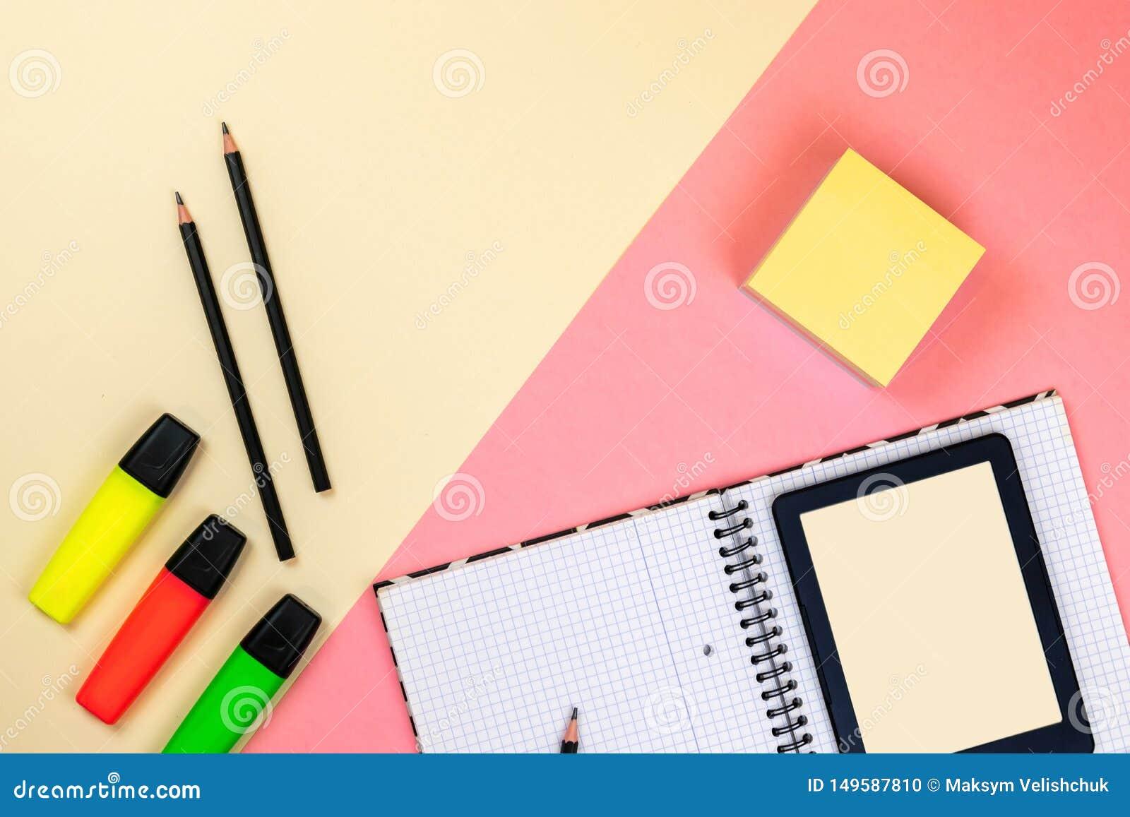 Планшет, школьные принадлежности, тетрадь и покрашенные отметки на пастельной розовой и бежевой предпосылке