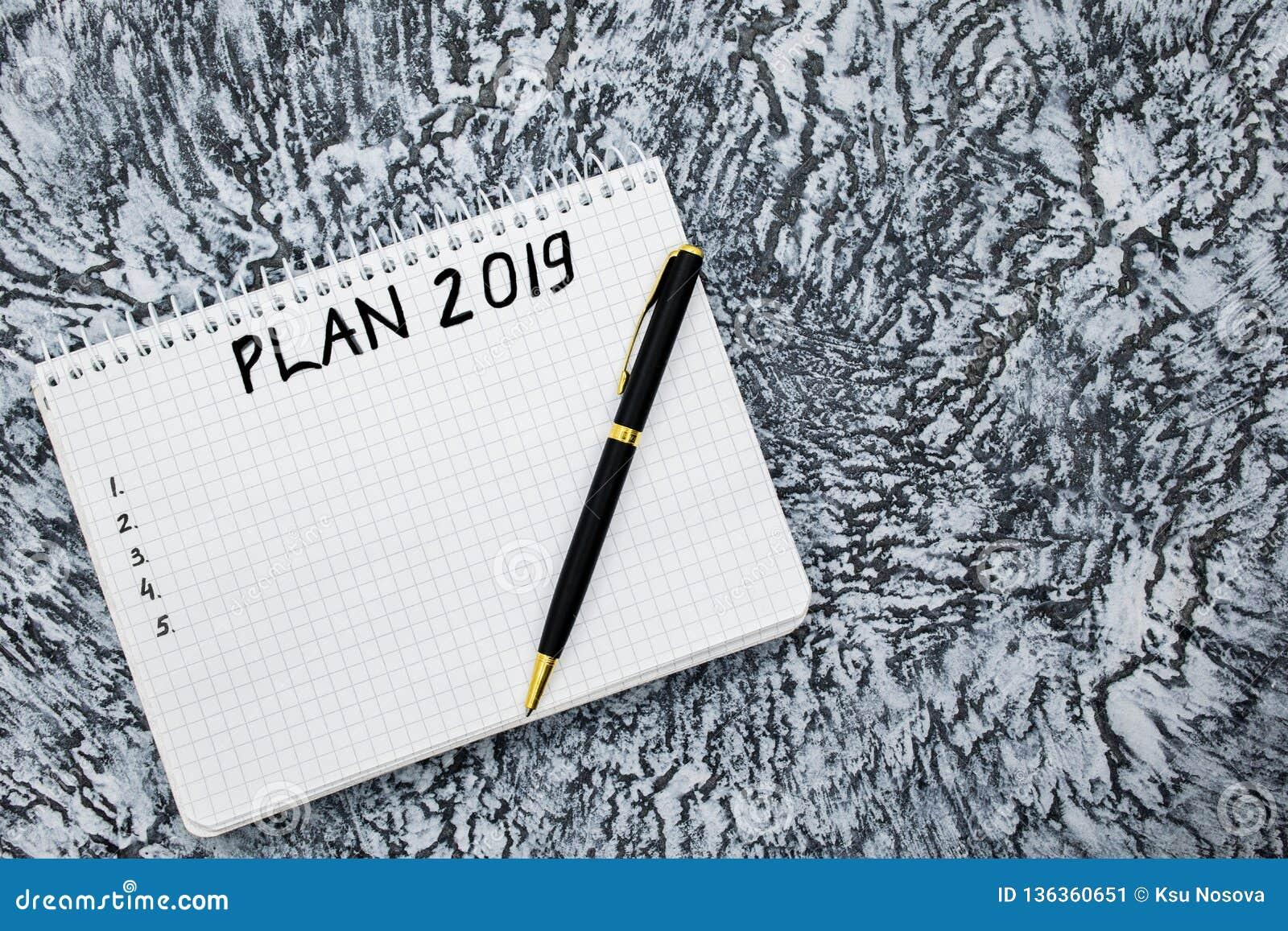 План на 2019, блокнот и ручка на текстурированной серой предпосылке