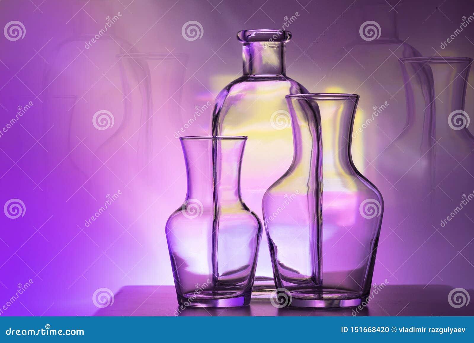 План 2 стеклянных ваз и бутылок на ярком пурпуре и желтая покрашенная предпосылка, горизонтальный план