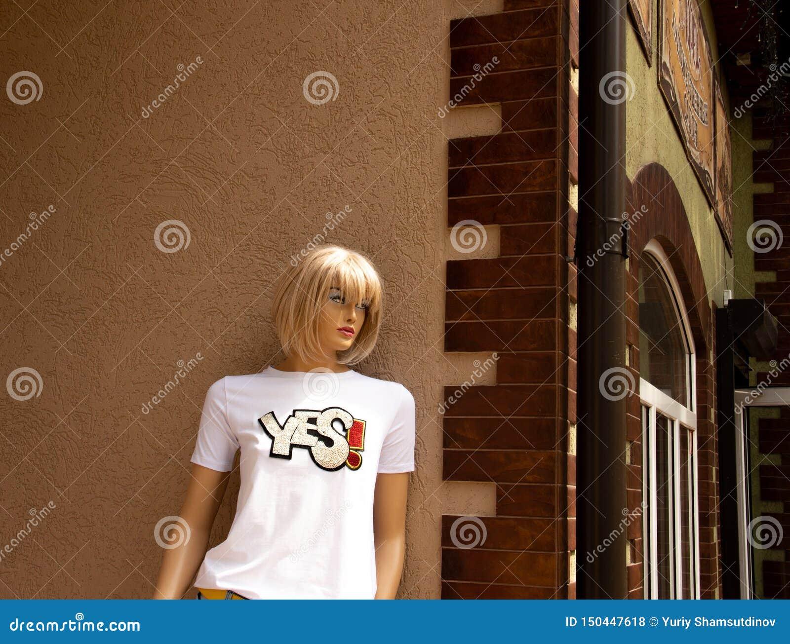 Пластиковая девушка ждет ее пластикового друга на угле улицы