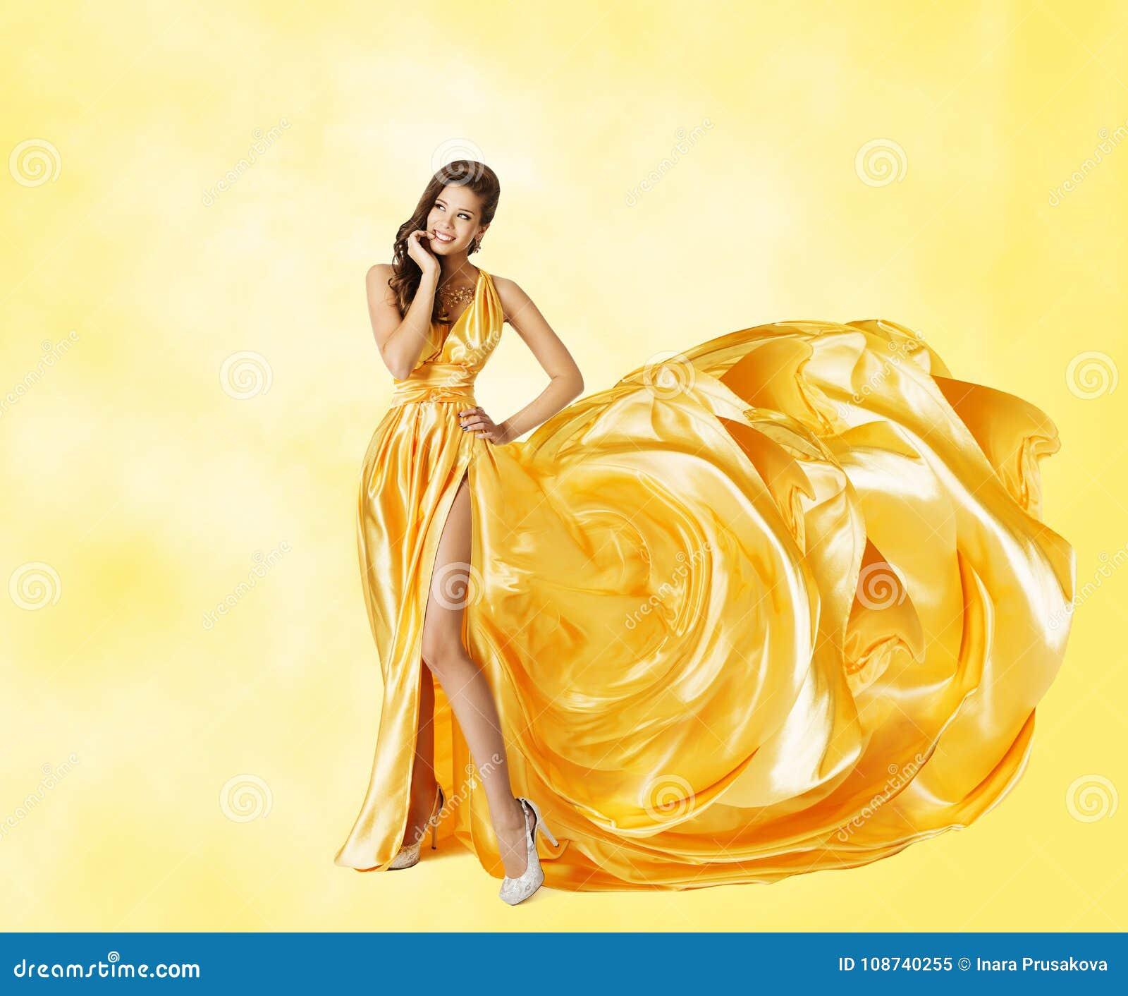 Платье желтого цвета женщины, счастливая фотомодель в элегантной длинной мантии