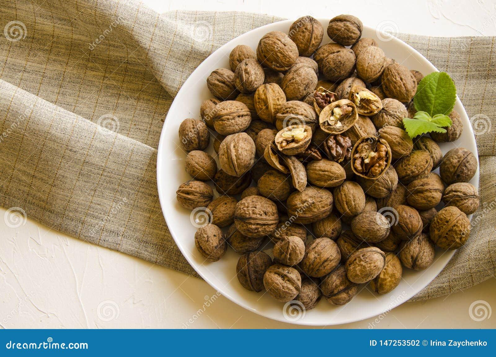 Плита с вкусными грецкими орехами на белой предпосылке
