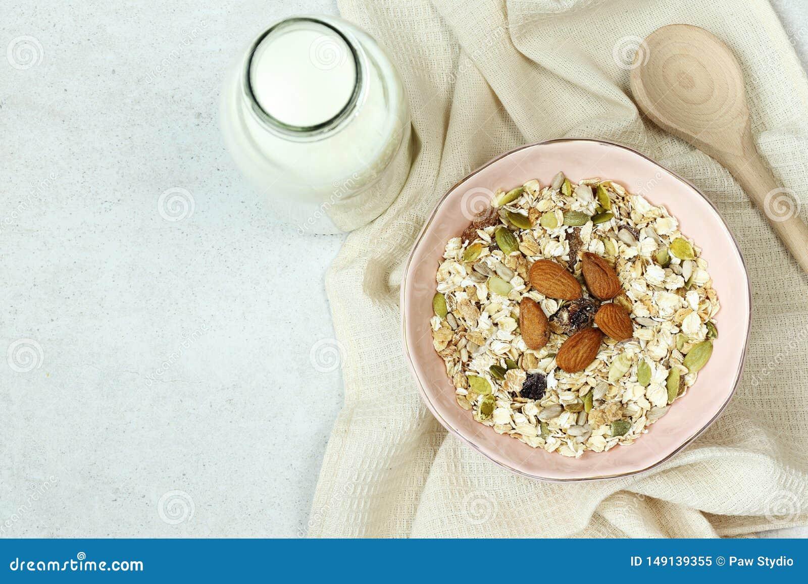 Плита с muesli, бутылка молока и деревянная ложка на серой конкретной предпосылке