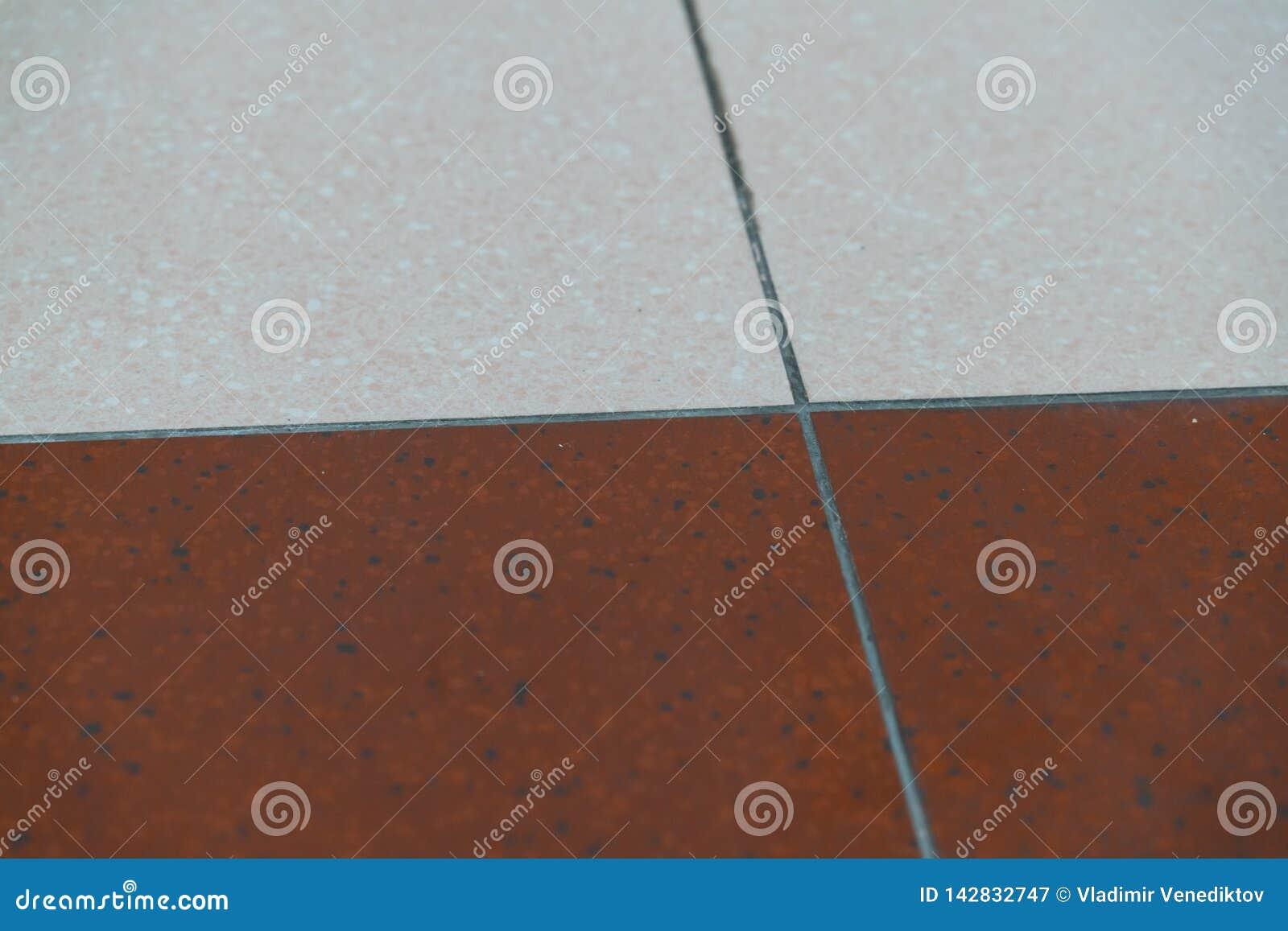 Плитки гранита коричневы и белы на поле как предпосылка Текстура гранита