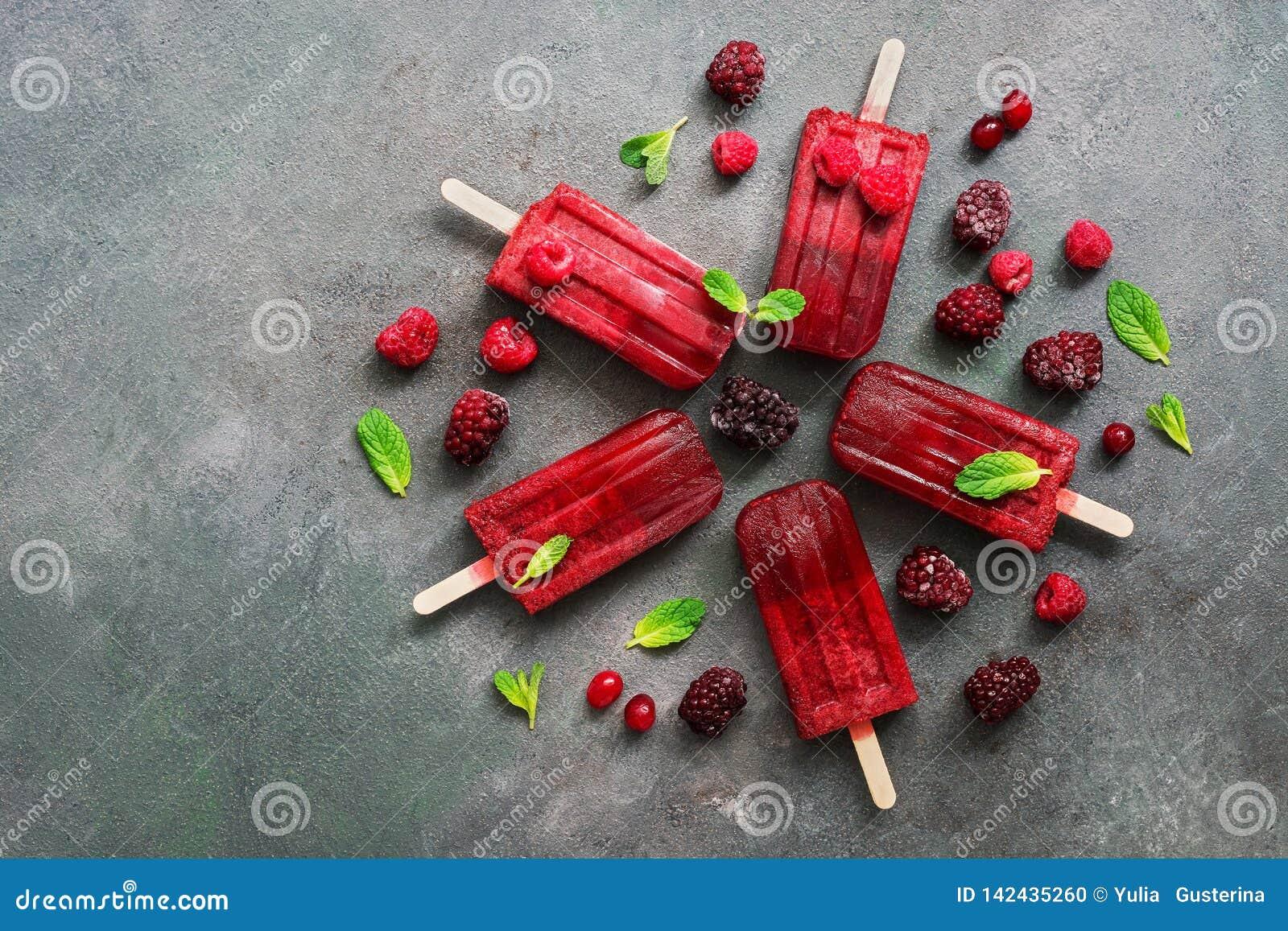 Плоские положенные домодельные popsicles мороженого ежевики поленик украсили ягоды и листья мяты на серой предпосылке Освежать