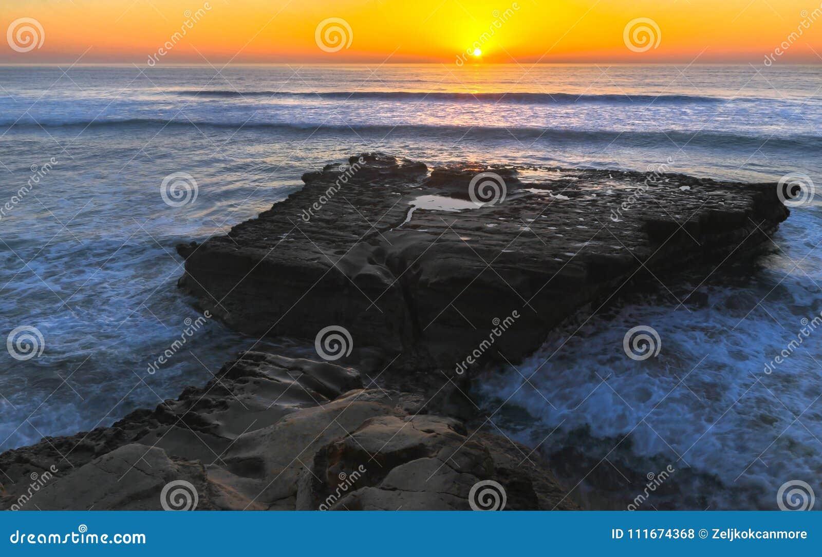 Плоский пляж положения Сан-Диего сосен Torrey захода солнца утеса и Тихого океана Калифорния