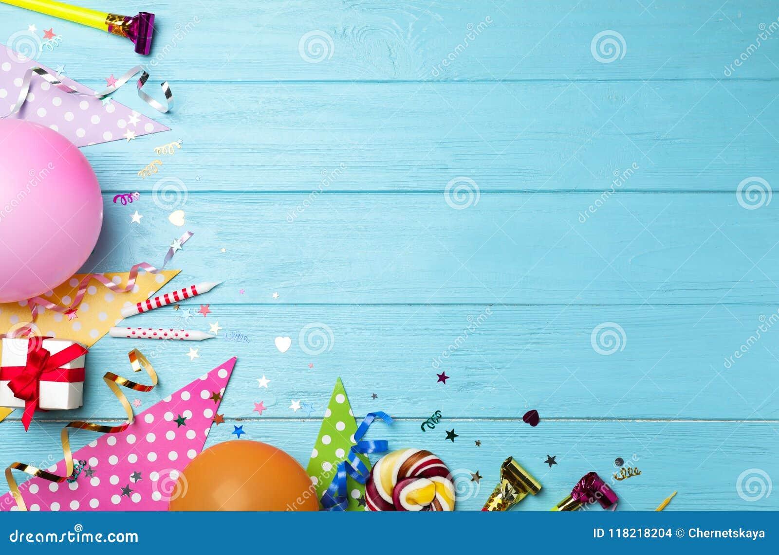 Плоский состав положения с деталями вечеринки по случаю дня рождения на голубой деревянной предпосылке