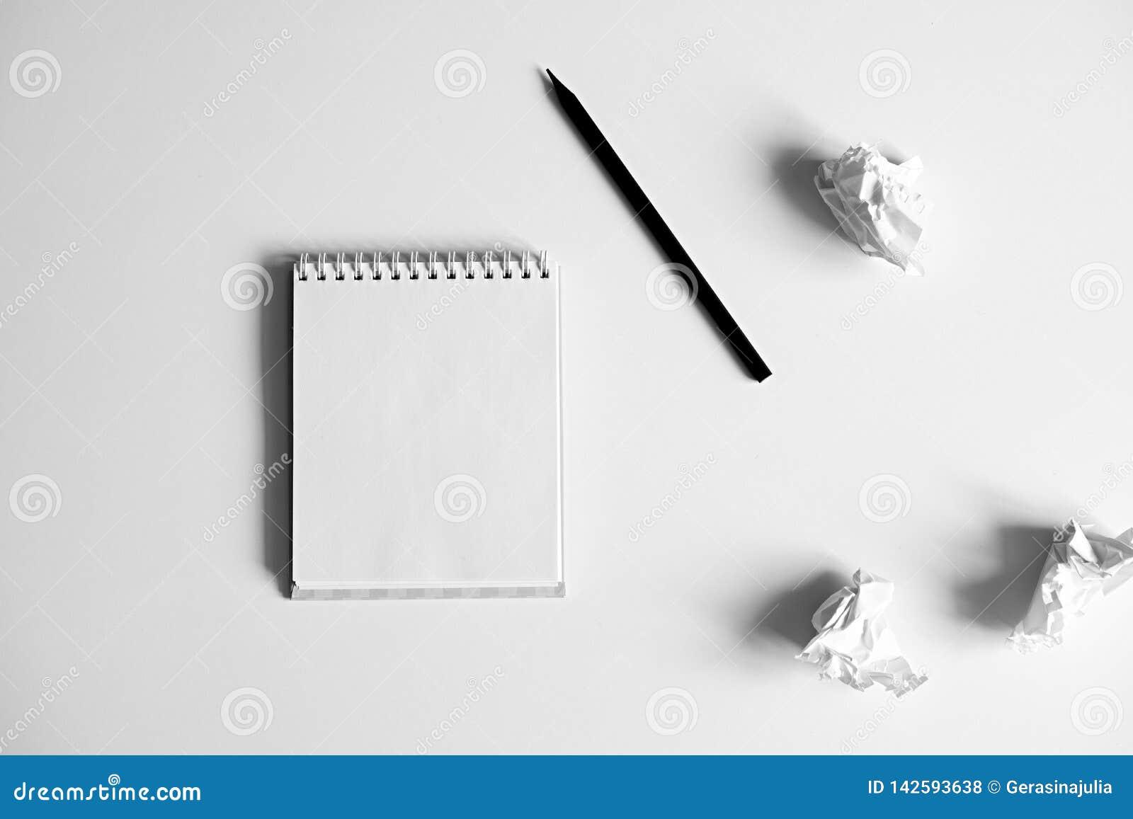 Плоское положение пустого белого блокнота, карандаша и скомканной бум