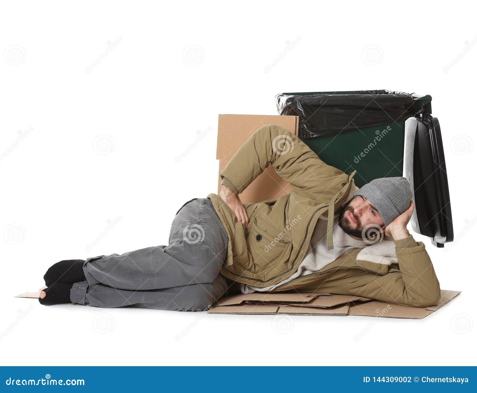 Плохой бездомный человек лежа около мусорного ведра