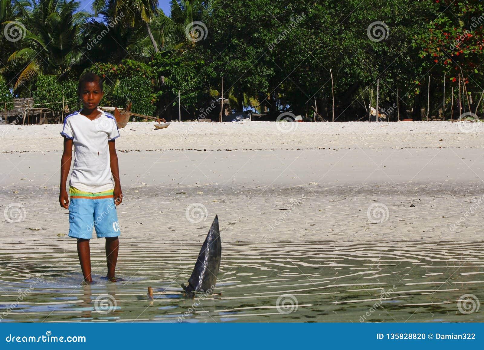 Плохой малагасийский мальчик играя с ручной работы кораблем