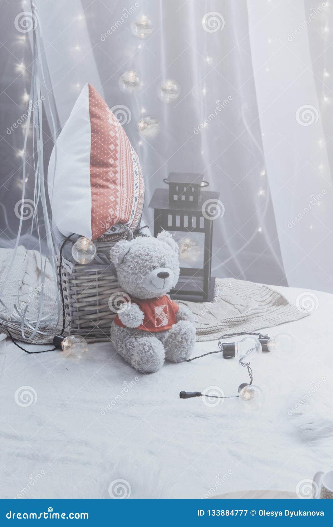 Плюшевый мишка сидя на кровати с подушками и декоративным электрофонарем никто Романтичное оформление спальни