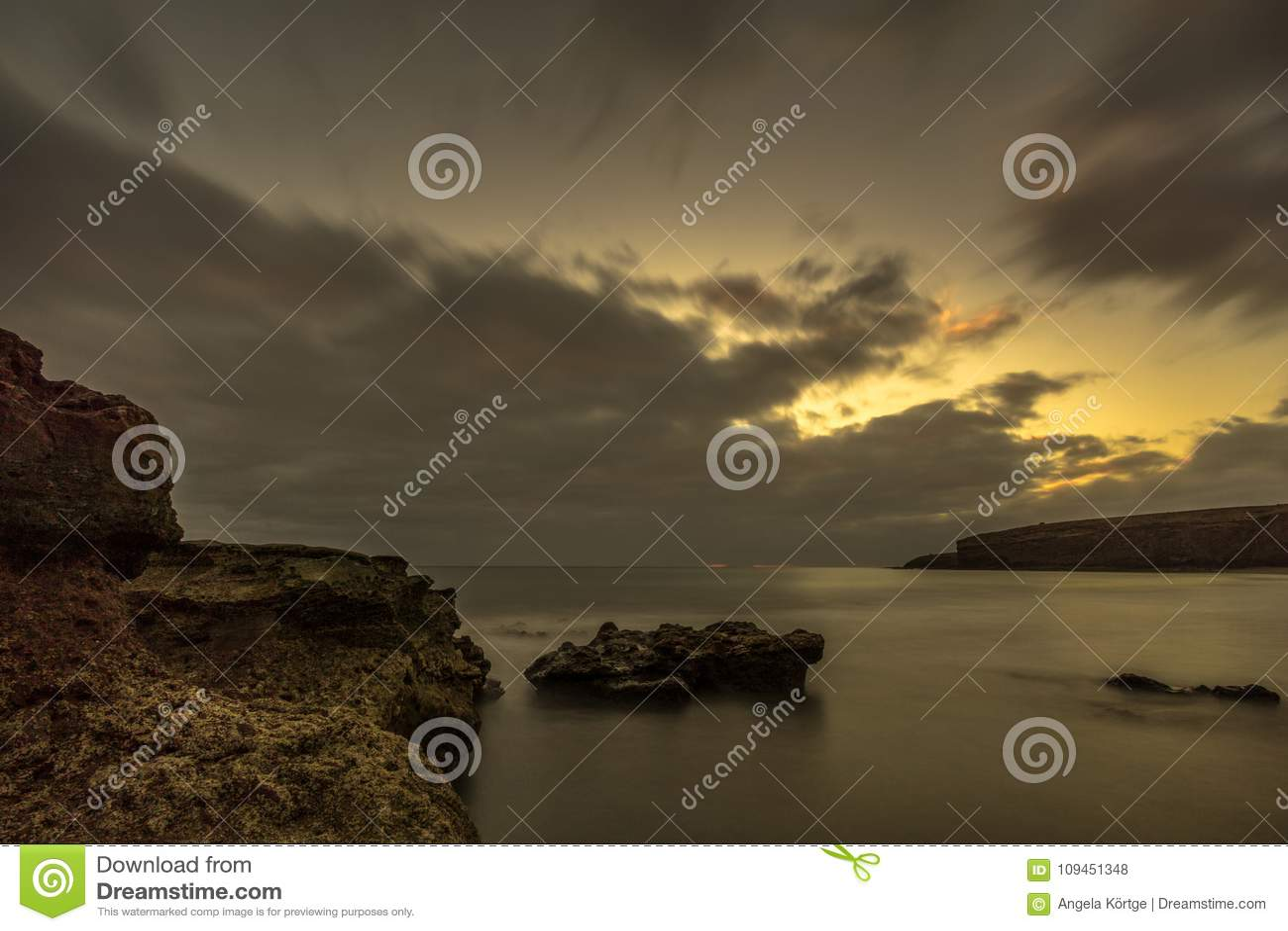 Пляж с большими камнями лавы на заходе солнца