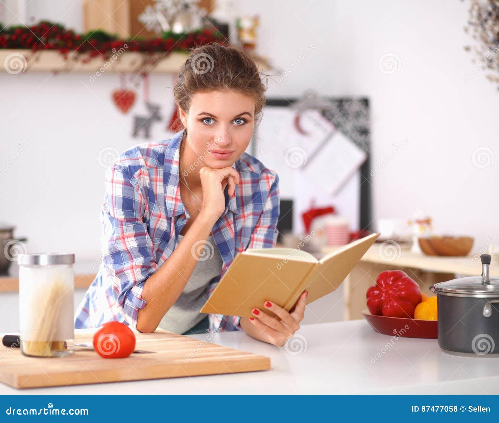 Поваренная книга чтения молодой женщины в кухне, ища рецепт