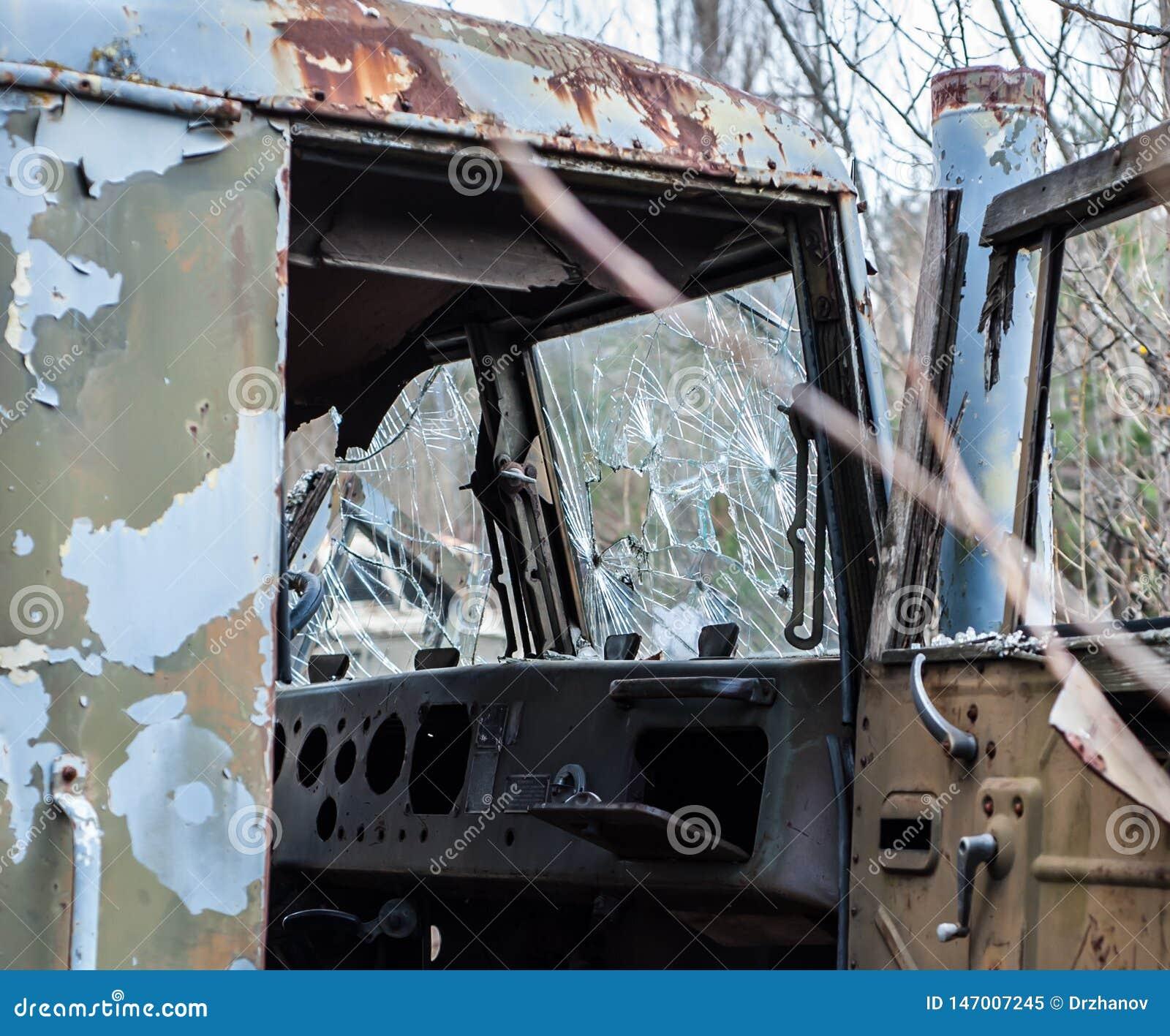 Поврежденная кабина со сломленным стеклом получившегося отказ прежнего военного следа, в зоне отчуждения Чернобыль