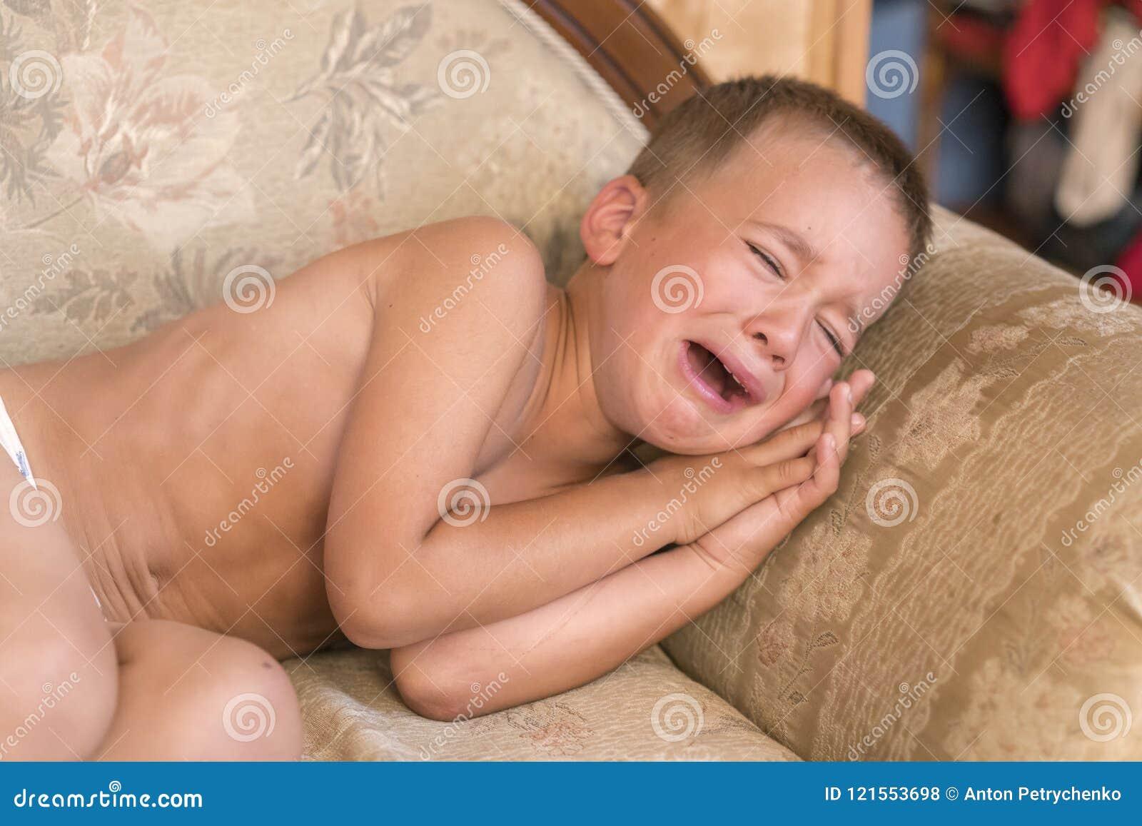 Подавленный мальчик плача на кресле дома Конец-вверх снял унылого мальчика плача на софе
