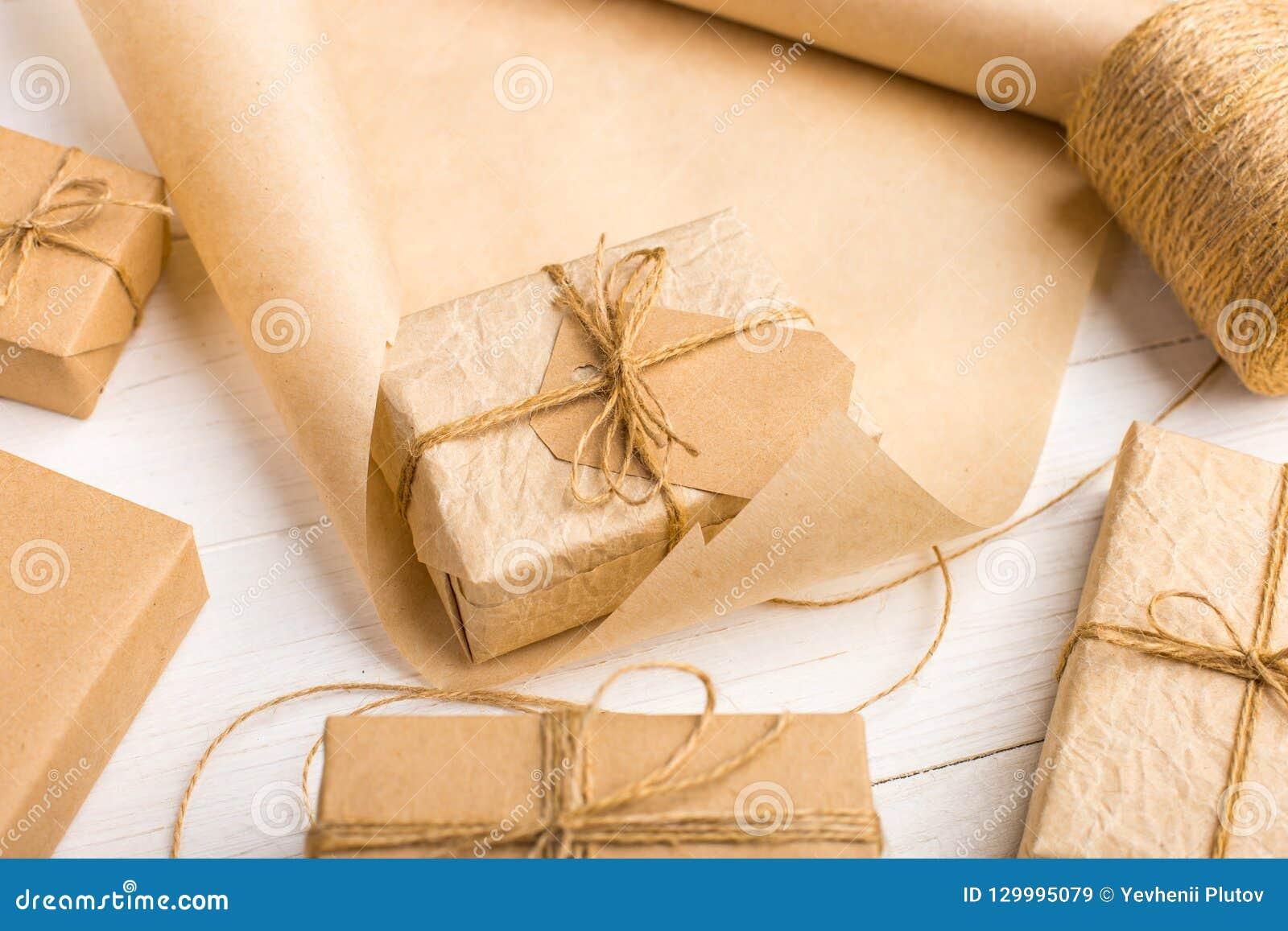 Подарки от бумаги Kraft на белой таблице с потоками и креном