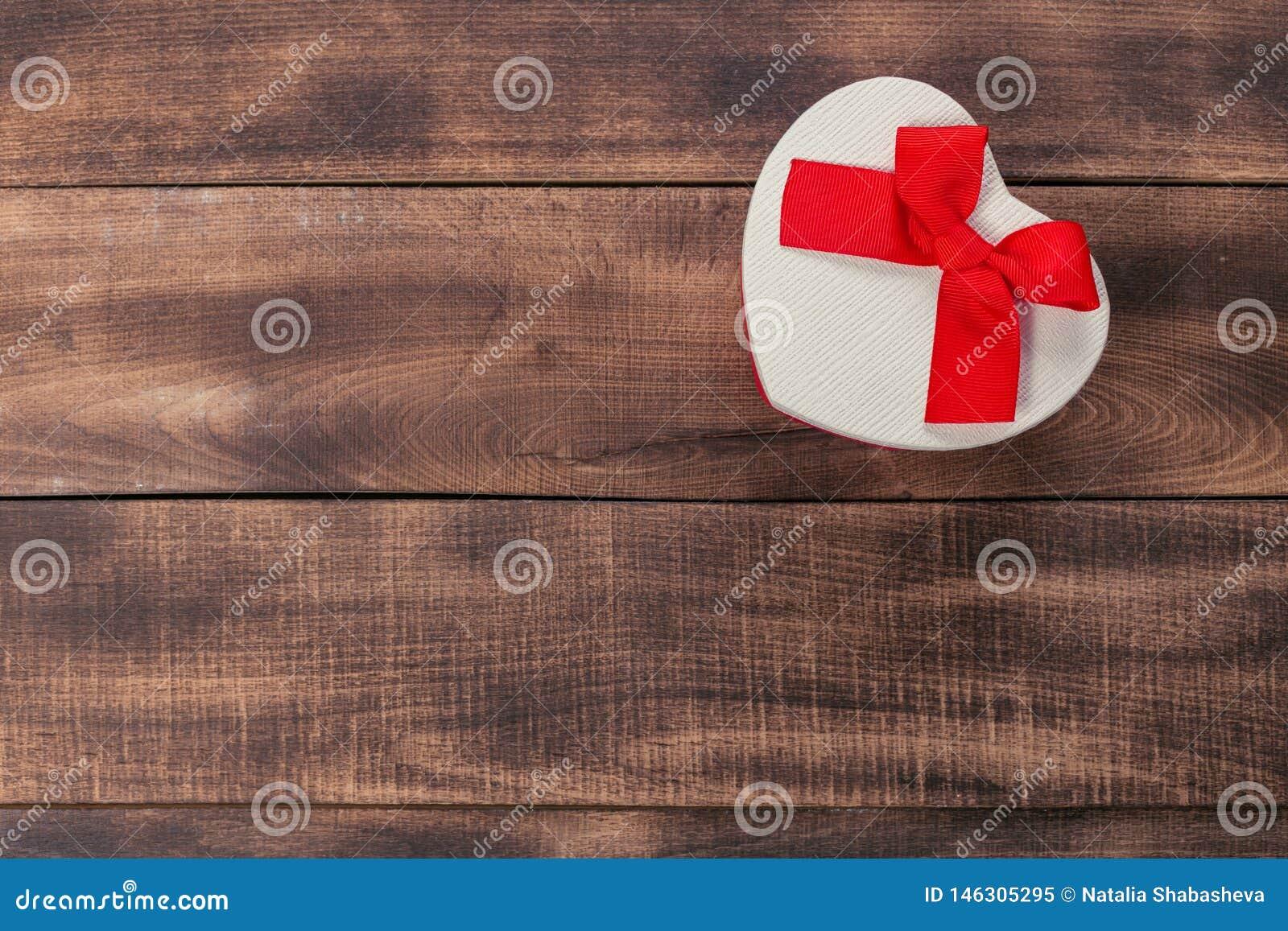 Подарки с красной лентой на деревянном столе