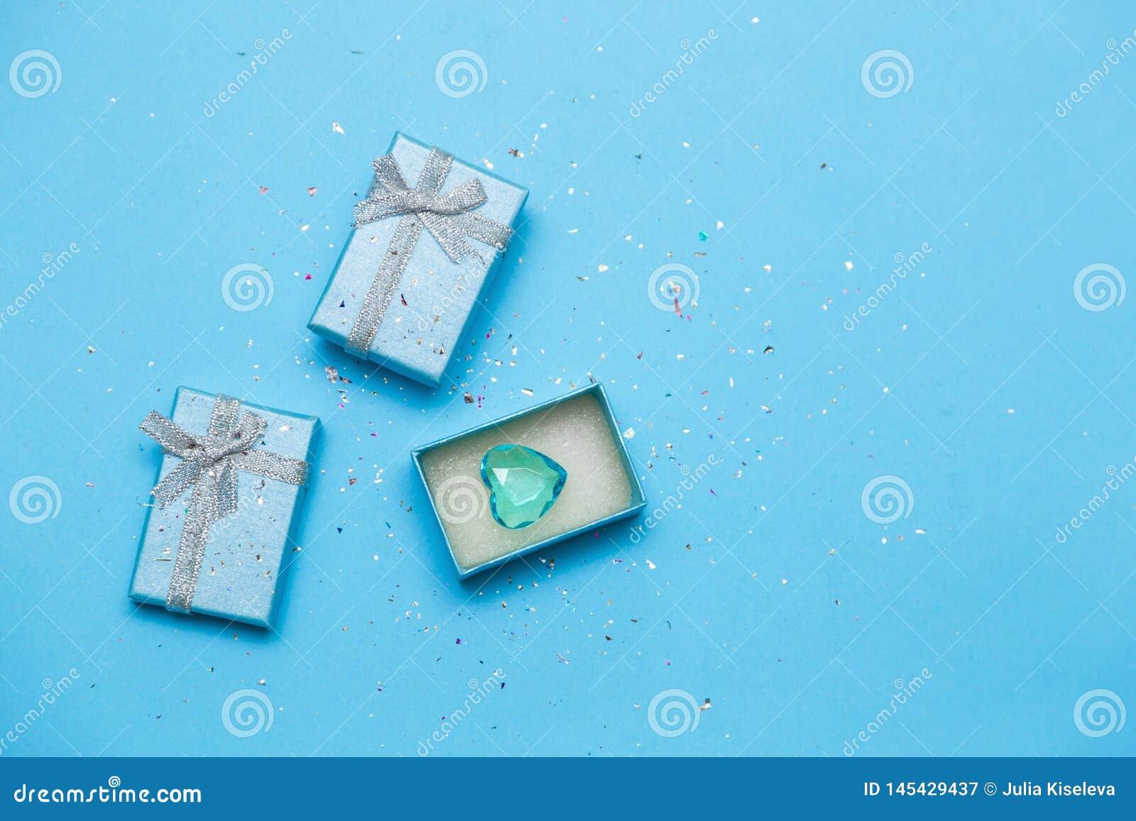 Подарок или подарочная коробка и голубое сердце на голубой предпосылк