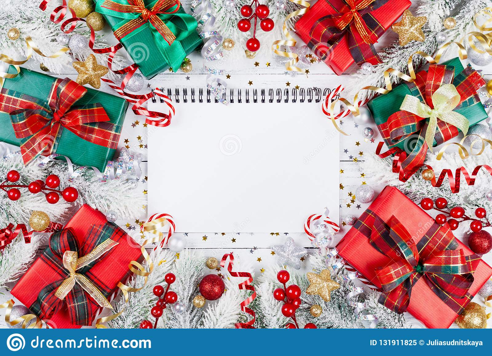 Подарок или присутствующие коробки, пустая тетрадь, снежная ель и украшения рождества на белом взгляде сверху деревянного стола П