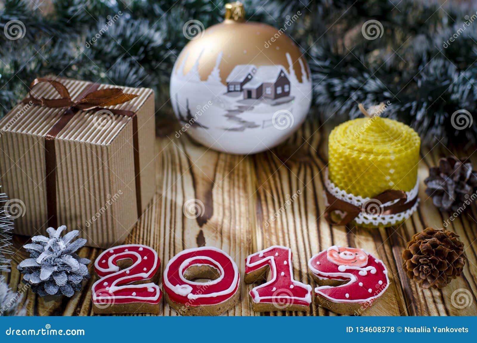 Подарок кладет на деревянный стол рядом со свечой, конусами и ангелом на фоне украшений рождества