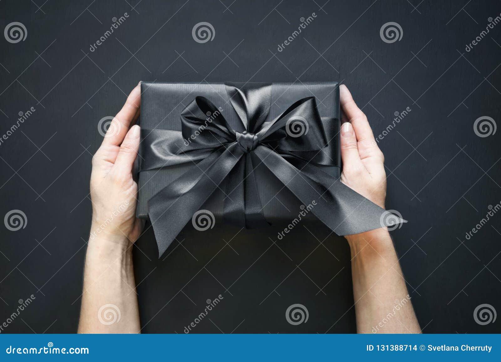 Подарочная коробка в оболочке в черноте в женской руке на черной поверхности Взгляд сверху