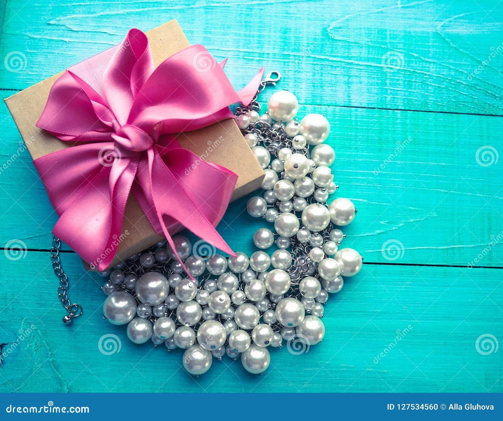 Подарочная коробка с розовым смычком ленты и украшения жемчуга на голубой деревянной таблице